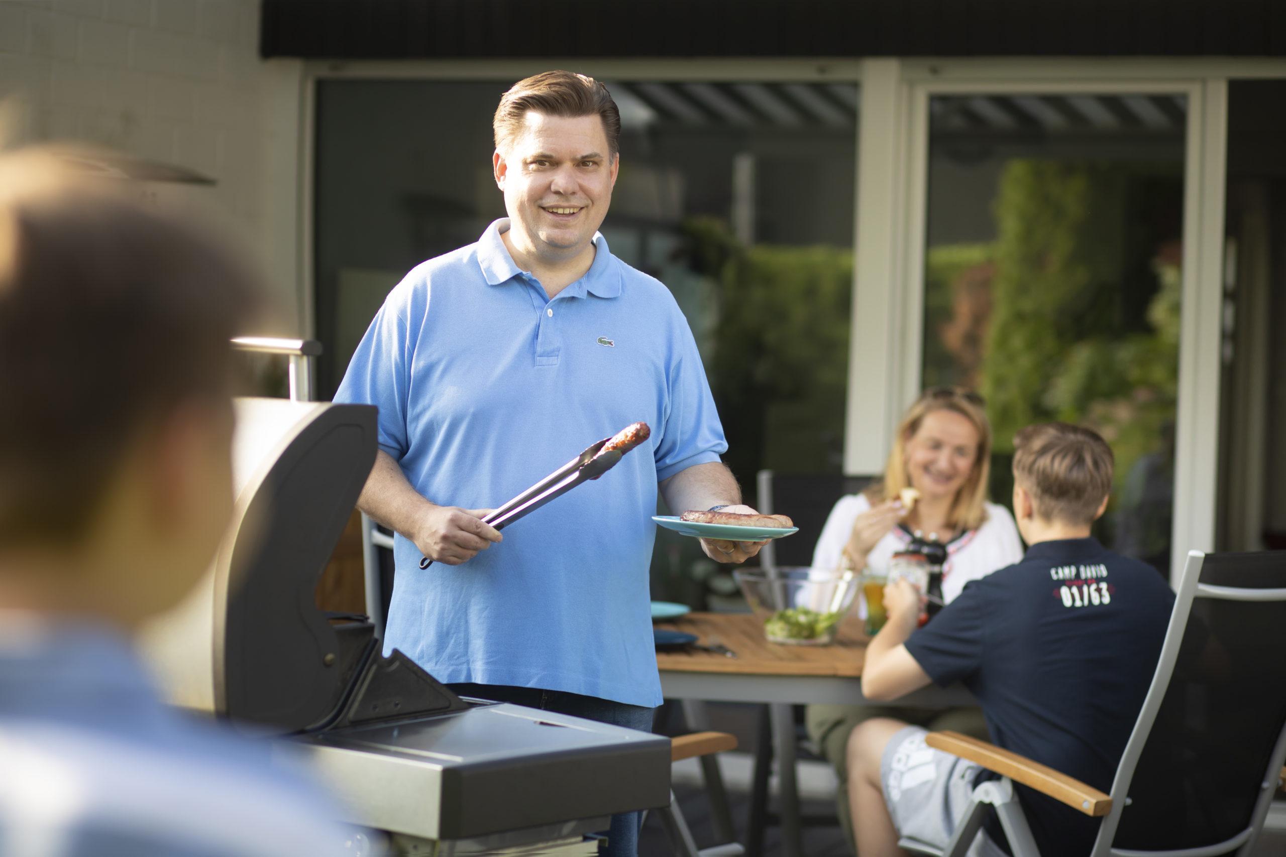 Stefan Schmitt steht hinter einem Grill, im Hintergrund sitzen ein Junge und eine Frau essend am Tisch