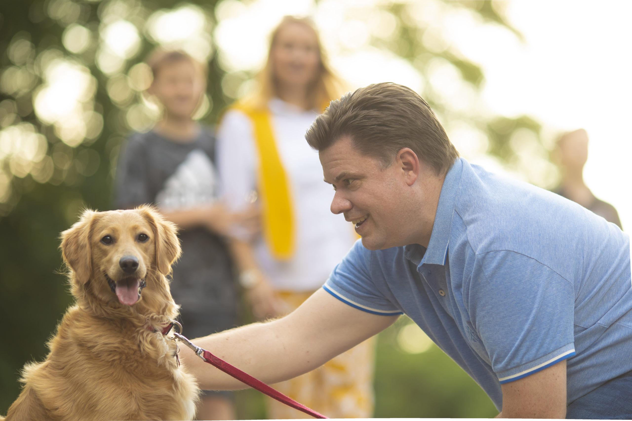 Stefan Schmitt streichelt seinen Hund, Frau und Sohn sind unscharf im Hintergrund