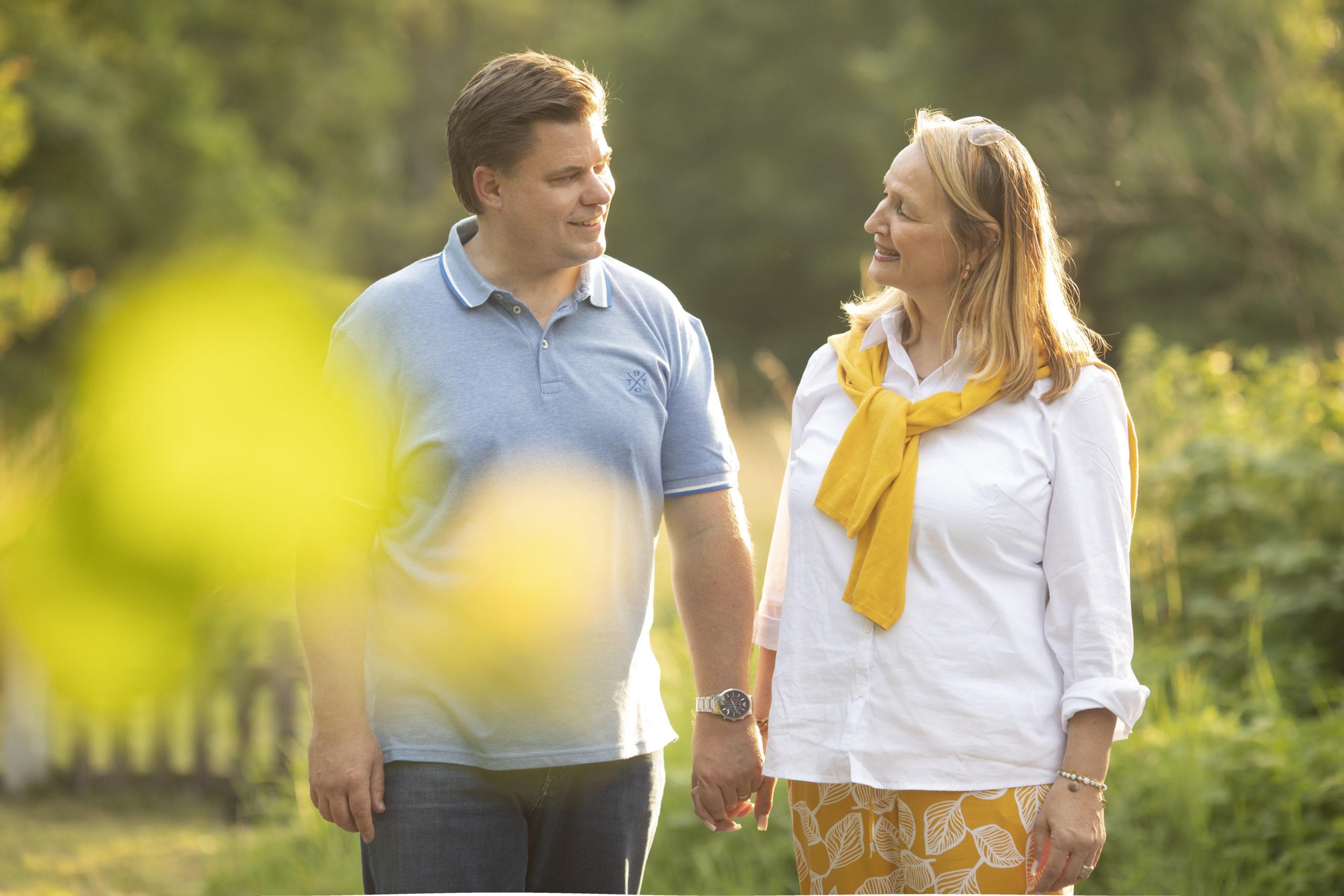 Stefan Schmitt und seine Frau blicken sich Händchen haltend und lächelnd an, während sie durch die Natur spazieren