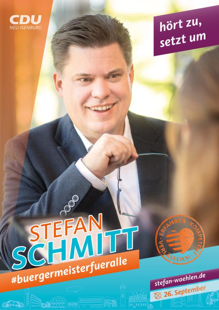 Wahlplakat, Stefan Schmitt hält Brille in der Hand und spricht mit einer Frau, deren Hinterkopf man unscharf im Vordergrund sieht. Text: hört zu, setzt um. Erfahren, kompetent, verlässlich